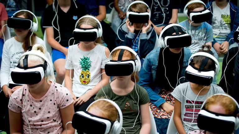 Niet de Tilburgse scholieren uit het verhaal, maar wel kinderen met een virtual reality-bril. (Foto: ANP)