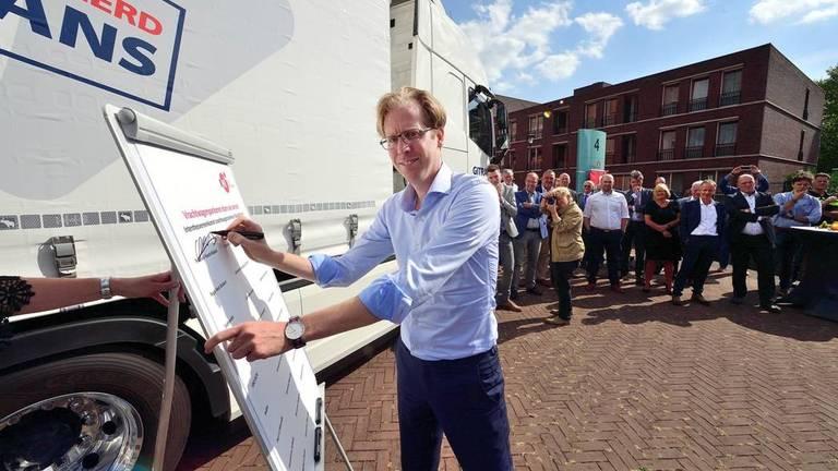 """Gedeputeerde Christophe van der Maat tekent de overeenkomst """"Vrachtwagenparkeren in West-Brabant""""."""