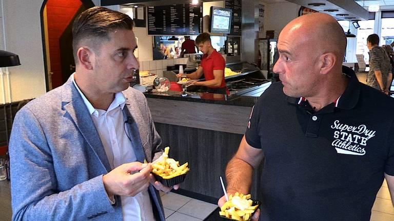 Verslaggever Ronald Sträter eet samen met John Karelse een frietje met.