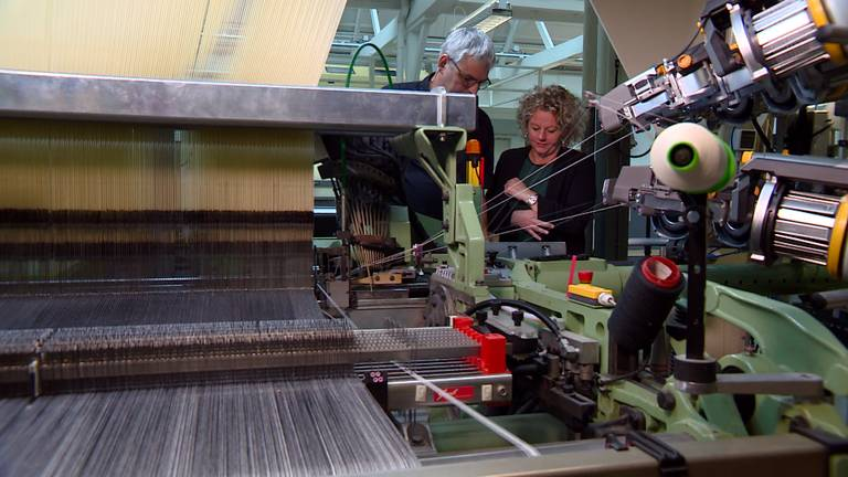 Babette en Michel bij een van de moderne weefmachines van het Textielmuseum.