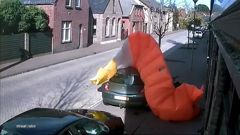 De parachutist valt eerst op een dak en komt daarna op straat neer.