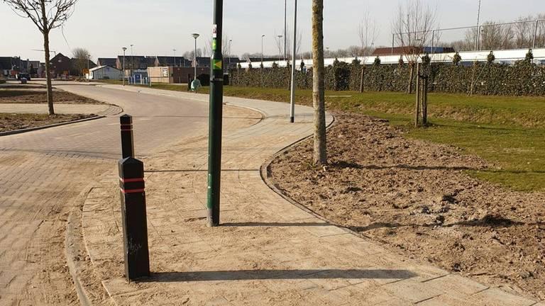 Twee lantaarnpalen midden op een nieuw trottoir in Almkerk (foto Sija op 't Hof  Twitter)