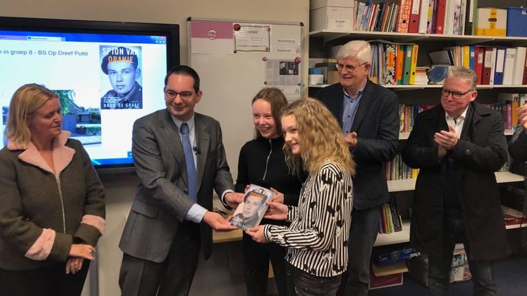 Burgemeester Adriaansen geeft het boek Spion van Oranje aan leerlingen van groep 8