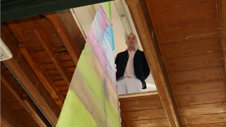 Stijn Ank bij het kunstwerk waarvoor hij een gat in het plafond van Club Solo liet zagen.