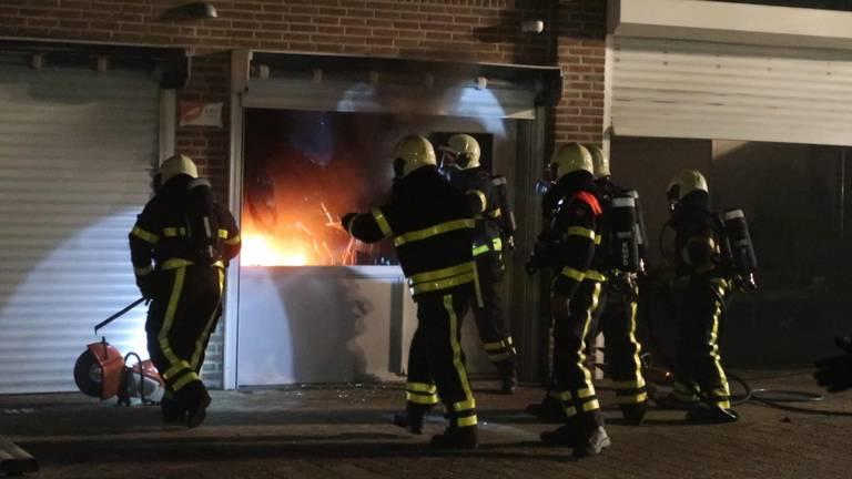 De politie breekt de deuren van de garageboxen open. (Foto: Perry Roovers/SQ Vision)