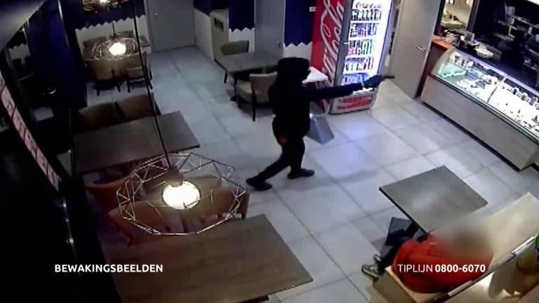 Een van de jongens liep met getrokken pistool naar binnen.