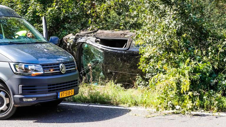 De auto van de vrouw ligt op z'n zijkant tegen een boom (foto: Dave Hendriks / SQ Vision).