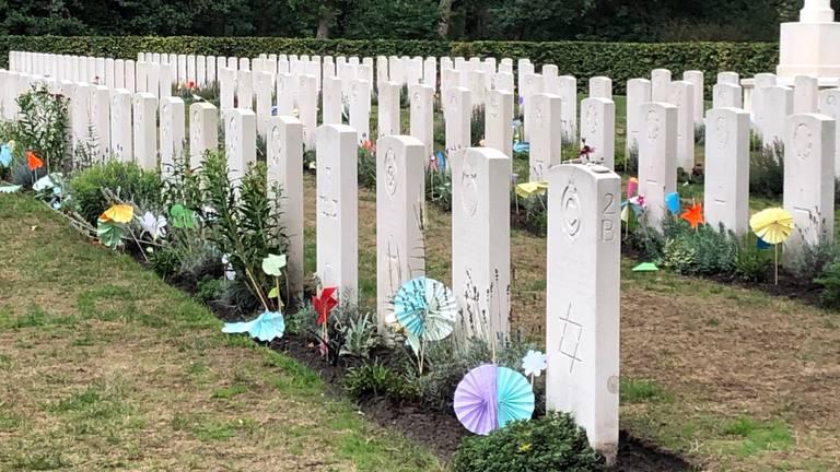 Papieren bloemen bij de oorlogsgraven. (Foto: René van Hoof)