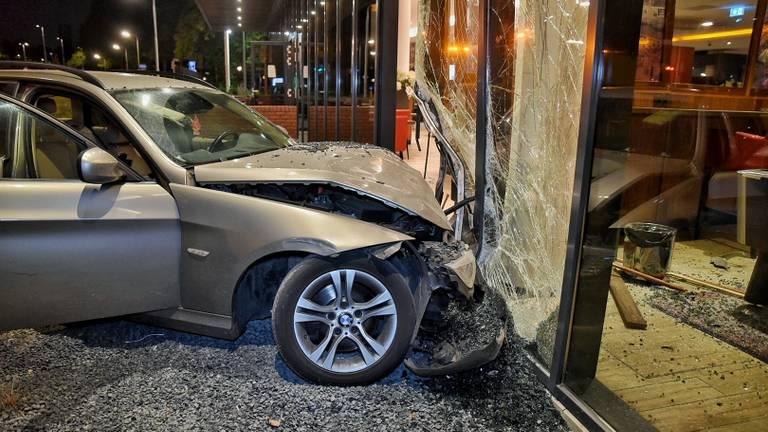 De auto eindigde tegen de gevel van het Bastion Hotel in Tilburg. (Foto: Toby de Kort)
