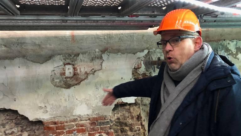 Archeoloog Glaudemans bij de buitenmuur van De Kleine Winst