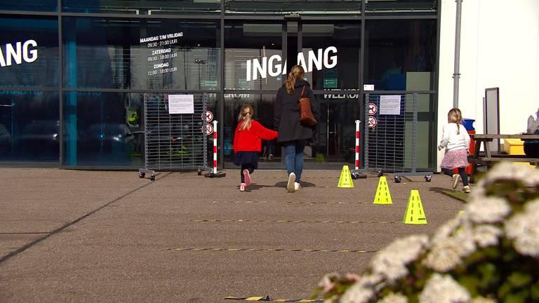 Klanten die wachten voor de winkel moeten afstand van elkaar houden (foto: Jos Verkuijlen).