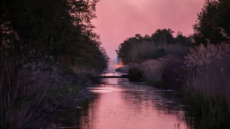 De lucht kleurt boven het Deurnes Kanaal door de hevige brand bij zonsondergang (foto: Joyce van Dijk Fotografie)