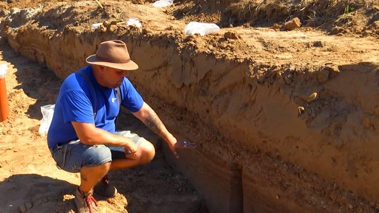 Archeoloog Nico van der Feest laat stukjes van de weg zien.