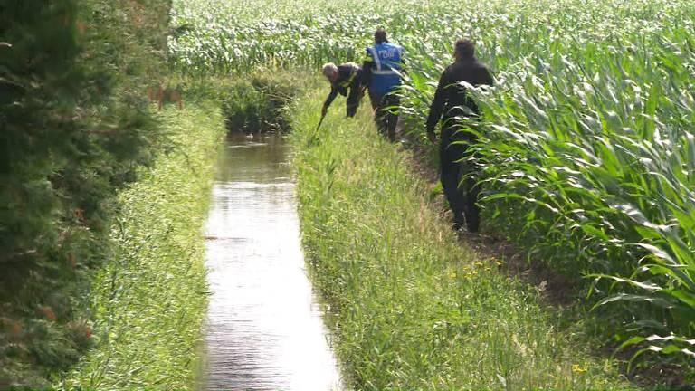 Agenten doorzoeken de sloot naast het huis (foto: Omroep Brabant).