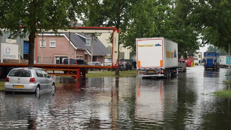 Ook vrachtwagens moeten zich een weg door het water banen (Foto: Erik Haverhals).
