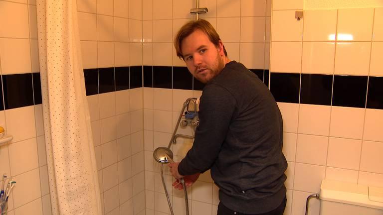 Lars bij zijn douche waaruit alleen koud water komt.