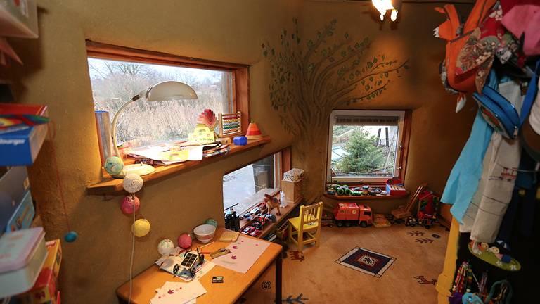 Kinderkamer van Ilja, met een laag raam zodat hij naar buiten kan kijken. Op de muur een boom met echte blaadjes.