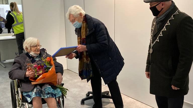 Zuster Marcelliana ontvangt na haar vaccinatie bloemen van de burgemeester (foto: gemeente Meierijstad).