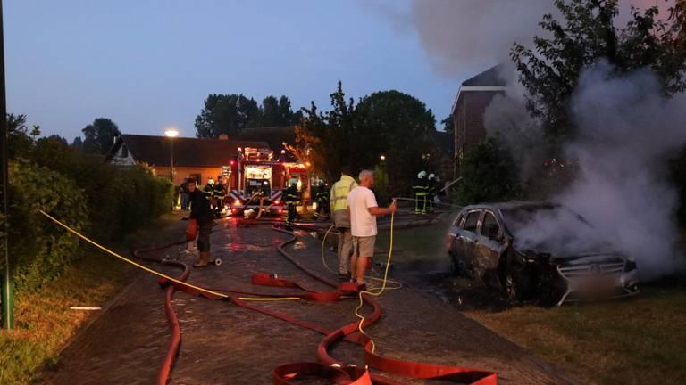 Mensen proberen bij de woning- en autobrand in Genderen te redden wat er te redden valt (foto: FPMB/Erik Haverhals).