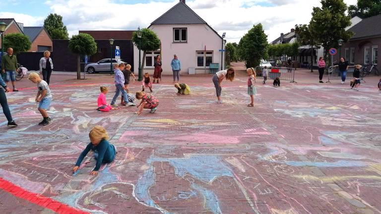 Kinderen druk aan het tekenen op het kerkplein.