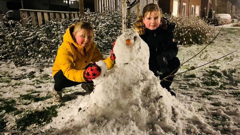 Fenna en Demi met hun zelfgemaakte sneeuwpop in Liempde (foto: Sander van Gils)..