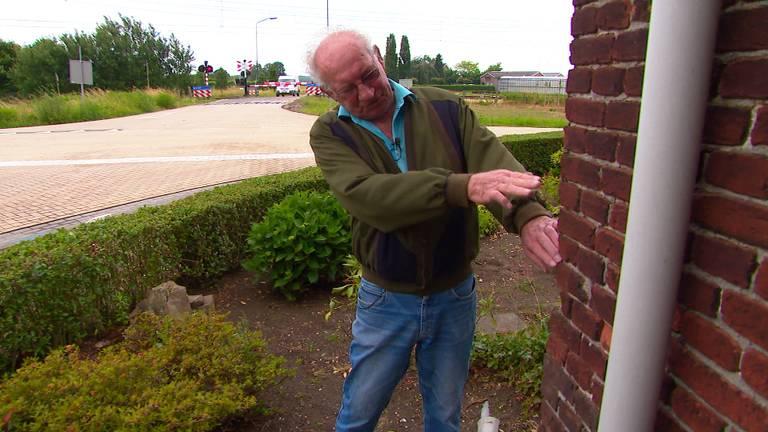 Gerard wijst aan waar de auto tegen zijn gevel belandde (foto: Omroep Brabant).