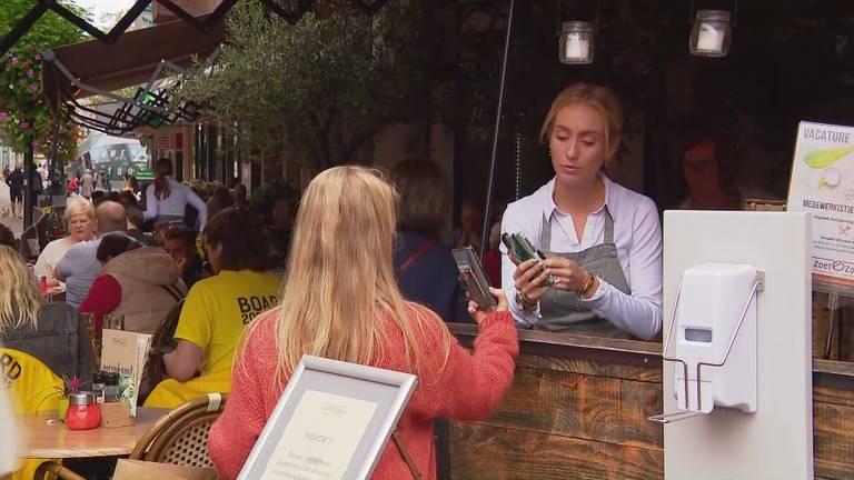 Een medewerker van een Eindhovens café doet een coronacheck.