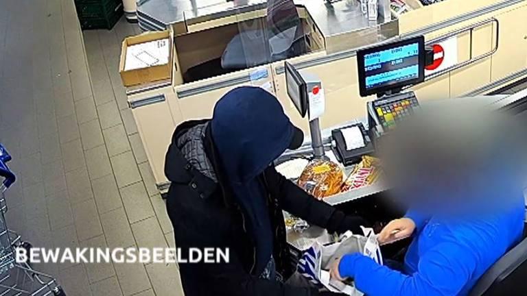 ALDI-medewerker vult de plastic tas met geld en sigaretten (foto: politie).