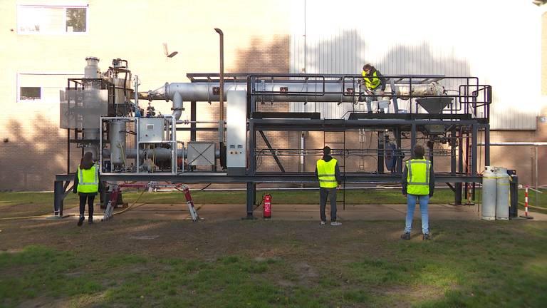 Een deel van studententeam SOLID bij hun ijzerverbrandingsinstallatie.