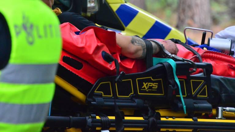 De bestuurder met handboeien op de brancard (foto: Walter van Bussel / SQ Vision).